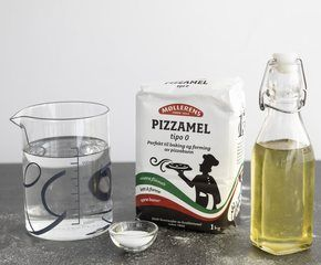 <p>Rør gjæren ut i vannet, tilsett de øvrige ingredienser og elt deigen godt, gjerne 7-8 min. i en kjøkkenmaskin.Del deigen i 200g biter som rulles til runde boller, sett disse på kjøl 2-3 timer tildekket med plast, du kan også begynne å kjevle med engang hvis ikke du har tid å vente</p>